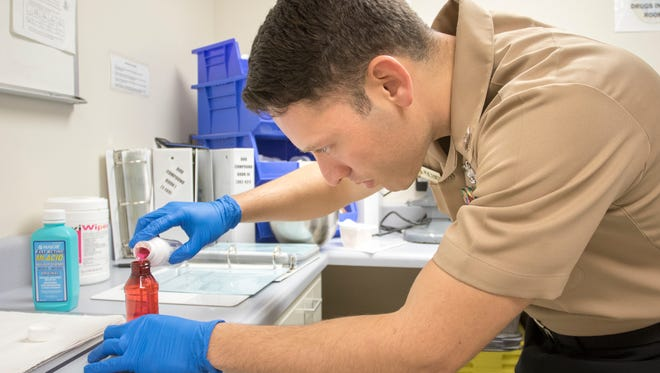 Petty officer Dario Perezrincon, a corpsman and pharmacy technician, prepares a medication at the Naval Hospital in Pensacola on Monday, December 5, 2016.