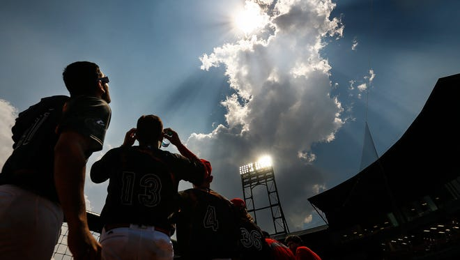 Redbirds players look up as a cloud rolls over the sun and moon as they engage in a total eclipse Monday. The game against New Orleans was halted briefly so players and fans could watch the event.