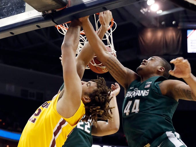Minnesota center Reggie Lynch, left, dunks the ball