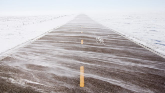 A file photo showing snow blowing across a road. More snow is expected on the Sierra crest a storm moves through the region over the upcoming weekend, forecasters say.
