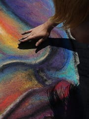 An artist uses her fingers as she works on her drawing Sunday during Chalkfest at The 400 Block in downtown Wausau.