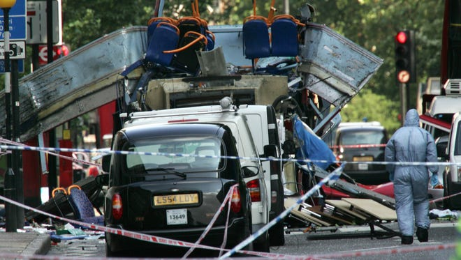 A forensic officer walks next to the wreckage of a double-decker bus with its top blown off and damaged cars scattered on the road at Tavistock Square in central London after the terrorist attack on July 7, 2005.