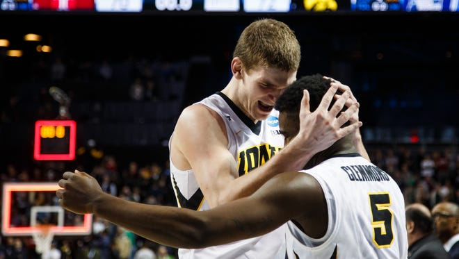 Adam Woodbury and Anthony Clemmons celebrate Iowa's 72-70 overtime win over Temple.