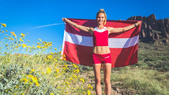 Ariana Hilborn of Greendale poses with the Latvian flag. She will run the marathon for her ancestral home country in the 2016 Olympics.
