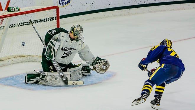 The puck hits the back of the net in the shoot-out giving Cooper Marody ,right, and his Michigan team the win over MSU and Ed Minney Saturday January 21, 2017 in East Lansing.  KEVIN W. FOWLER PHOTO