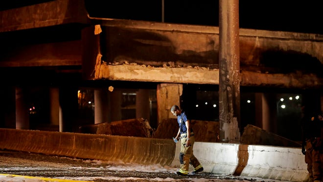 A firefighter walks by the section of an overpass that collapsed from a large fire on Interstate 85 in Atlanta on Thursday, March 30, 2017. Atlanta officials say a massive fire that burned for more than an hour caused the collapse of the interstate overpass. Georgia Gov. Nathan Deal has issued a state of emergency for the county.