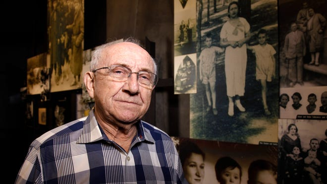 On Feb. 20, 2014, at the Dallas Holocaust Museum/Center for Education, Max Glauben  of Dallas stands in front of some of the photographs taken of him and his mother and brother in Poland. Max is in the photograph to his left, standing next to his mother. Max is on her right.