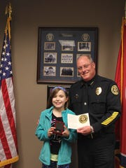 Deputy Chief Parr presents Jenna with the CPD Coin and the CPD Patch.