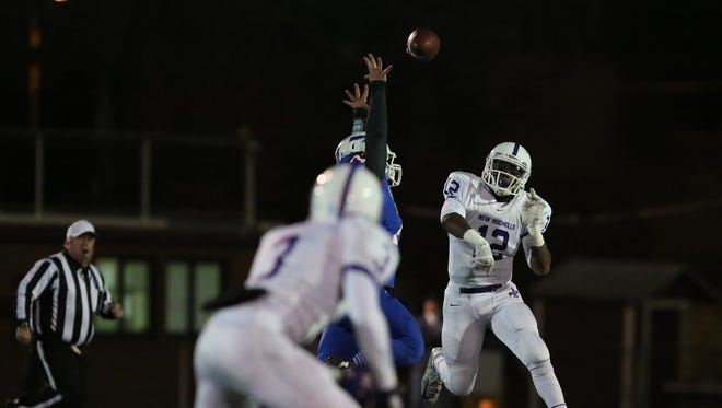 New Rochelle quarterback Greg Powell (12) throws a pass to Jayson Prince (3)  during the NYSPHSAA Class AA state semifinal football game against Saratoga Springs at Dietz Stadium in Kingston on Saturday, Nov. 21, 2015.