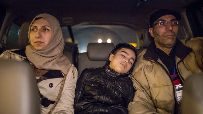 Arab Buteh, 8, falls asleep sitting between his parents Nayef Buteh, right, 45, and Feryal Jabur, 41. They are refugees from Syria on their way to a hotel after arriving at Detroit Metro Airport Thursday, Nov. 19, 2015.