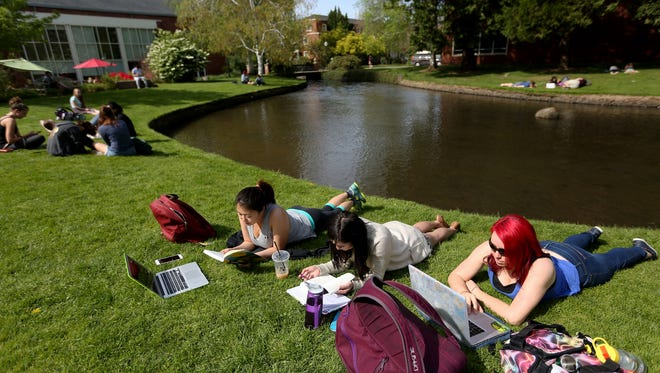 Seniors, from left, Beatrice McAlister, an environmental studies major, Cora Orm, an English major, and Shelly Kang, an environmental studies major, and others soak up the sun while studying at Willamette University in Salem on Wednesday, April 6, 2016. The high temperature is expected to reach 84 degrees on Thursday, which would be a record.