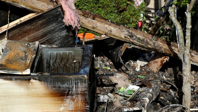 Scorched belongings lie on the grass outside a unit following a two-alarm fire overnight at the Oakbrook Apartments in Salem on Friday, April 15, 2016.