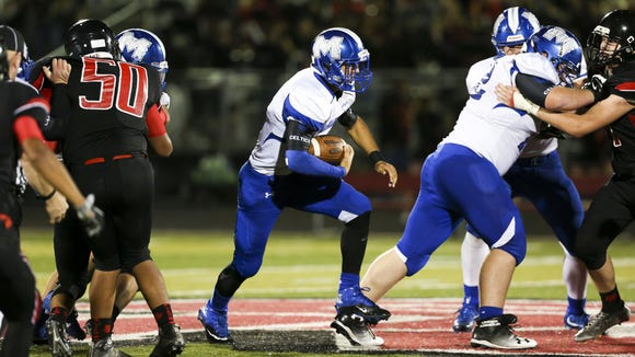 McNary quarterback Josiah Gilbert carries the ball up the middle in the season opening-game against North Salem on Friday, Sept. 2, 2016, at North Salem High School. McNary won the match-up 38-35.