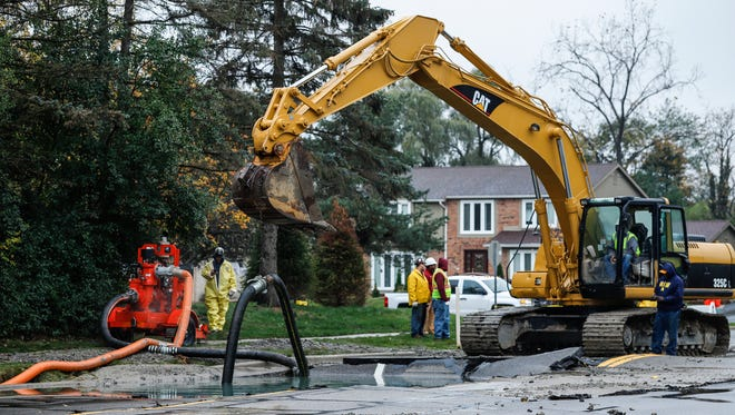Workers are examining the broken water main on West 14 Mile Road between Drake Road and Farmington Road in West Bloomfield Township, Tuesday, October 24, 2017.