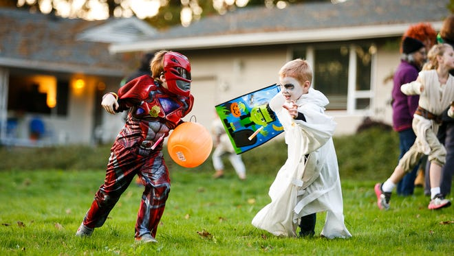 William Naumann, left, and Hudson Preece, right, play a game of tag at the annual Fairmount Halloween Parade in the Fairmount Hill neighborhood on Tuesday, Oct. 31, 2017, in Salem, Ore.