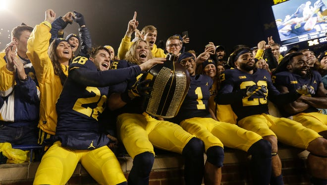Michigan defensive back Brandon Watson (28), defensive lineman Chase Winovich (15) and defensive back Ambry Thomas (1) celebrate their 33-10 victory over Minnesota with the Little Brown Jug at the student section at Michigan Stadium on Saturday.