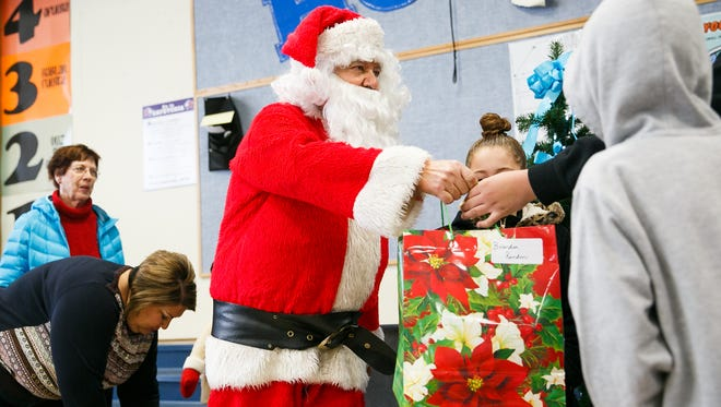 Pedro Rosales, dressed as Santa, hands out presents to families at Hoover Elementary for a Christmas event on Sunday, Dec. 17, 2017. Local restaurant La Margarita provided brunch for all of those in attendance, and purchased the presents that were given to families in attendance.