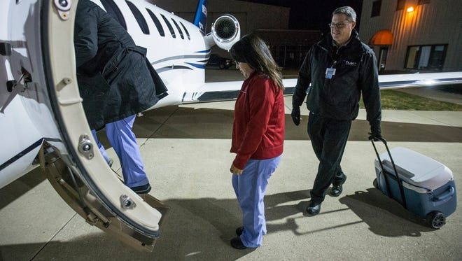From right, pilot Todd Ratzlaff pulls the organ procurement cooler as Ginny DeWitt and surgeon I-wen Wang, the medical team from IU Health, board the airplane to procure a heart and lung in Evansville, Ind., Monday, Nov. 20, 2017. The crew departed from Indianapolis International Airport at around 1 a.m. and returned with the procured organs just after 6 a.m. Ratzlaff is a first officer for Indiana Donor Network through its subsidiary aviation group, TxJet. There are pilots on-call 24/7 to transport organs from cities coast to coast for recipients in Indiana.