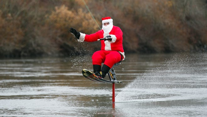 Dale Johnson water skis the Willamette River while dressed as Santa on Saturday, Dec. 23, 2017, by Wallace Marine Park. Johnson is using a hydrofoil water ski. This is the 33rd year that Johnson and his brother Steve have skied the river the Saturday before Christmas.