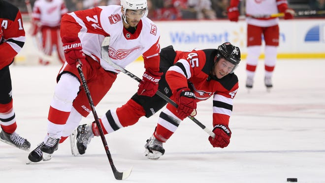 Detroit Red Wings left wing Andreas Athanasiou (72) and New Jersey Devils defenseman Sami Vatanen (45) race for the puck during the third period at Prudential Center.