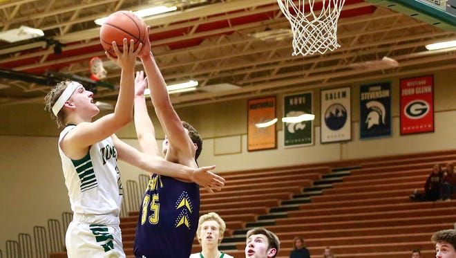 Howell's Josh Palo drives to the basket while DeWitt's Luke Hyde contests his shot.