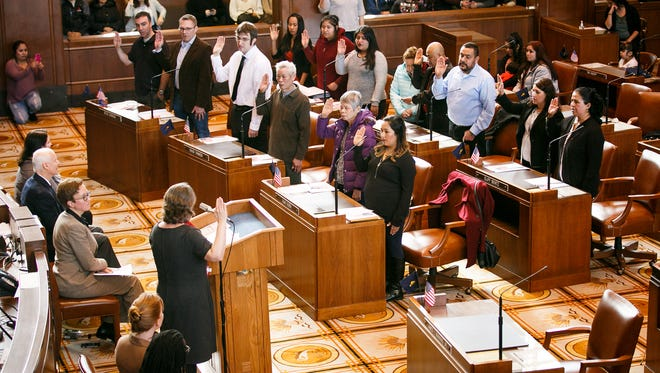 New citizens raise their right hands and take the Oath of Allegiance, completing the process to become a citizen of the United States, on Wednesday, Feb. 14, 2018, in the Senate Chamber at the Oregon State Capitol. Thirteen immigrants from six countries were naturalized during the ceremony, held on Oregon's 159th birthday.