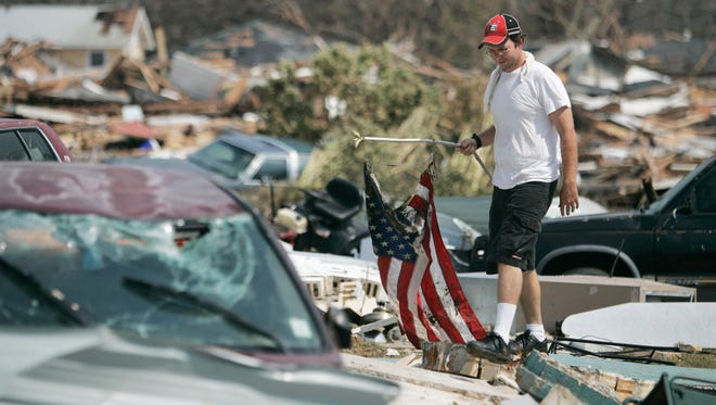 2005 Hurricane Katrina--Jason Davis finds an American flag in a neighborhood area in Biloxi, Miss. on Aug. 31, 2005.  Davis lost his house which was completely swept away accept for the front steps in the hurricane.