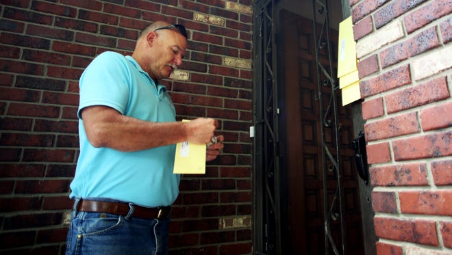 City code inspector Dale Wood issuing occupancy ordinance violation citations in this July 2014 file photo.