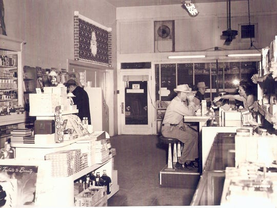 Customers sit at the soda fountain of MacAlpine's in its prime.