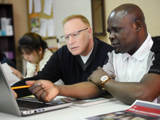 Lagu Rekpe, right, receives help from teacher Jim Veurink during class at the Global Institute of Lansing Monday, May 22, 2017, at First Presbyterian Church in Lansing. The Global Institute of Lansing offers adult refugees and immigrants a chance to earn their high school diplomas.
