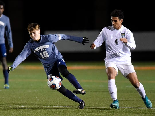 East Lansing's Almir Celovic, left, kicks the ball