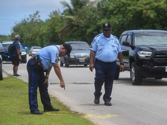 Guam Police Department officers Patrick Sanchez, right,