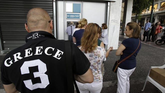 People stand in a queue to use an ATM outside a closed bank in Athens, Tuesday, June 30. Greek Finance Minister Yanis Varoufakis confirmed that the country will not make its payment due later to the International Monetary Fund. With banks shut and Greeks limited to cash withdrawals of 60 euros ($67) per day, long lines formed once more at ATM machines. (AP Photo/Thanassis Stavrakis)