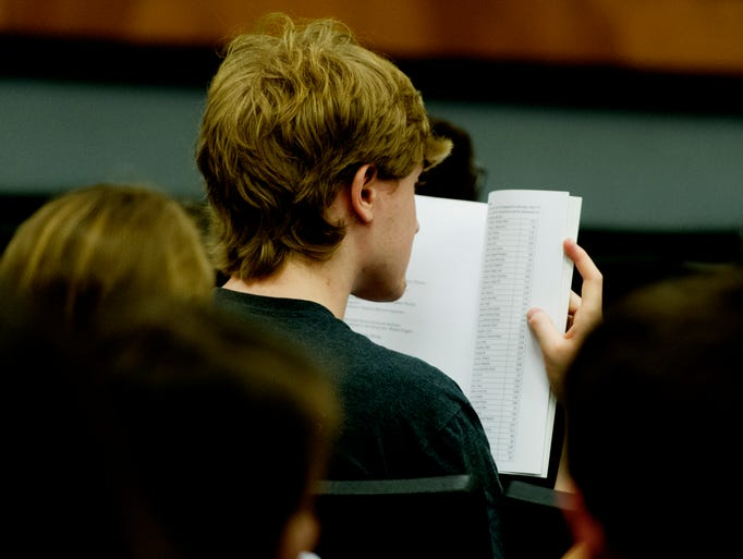 An attendee reads the catalog at the Undergraduate