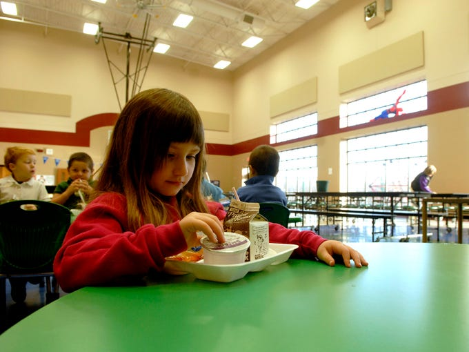 Preschooler, Anna Harris, 5, eats breakfast in the Brooks Elementary School cafeteria.  The large windows in the background help to cut down on electricity use by providing extra heat and light.  Bullitt County Public Schools has saved $1.5 million over the last five years by making its buildings more energy efficient. Nov. 19. 2013