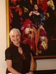 """With a painting of her in full Palm Springs Follies plumage, Judy Bell, 77, is happy to be on stage again, singing at the """"Thanks for the Memories"""" tribute show at the Palm Springs Air Museum."""