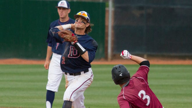 Dixie State second baseman Drew McLaughlin attempts a double play during their game against Azusa Pacific Thursday, April 14, 2016.