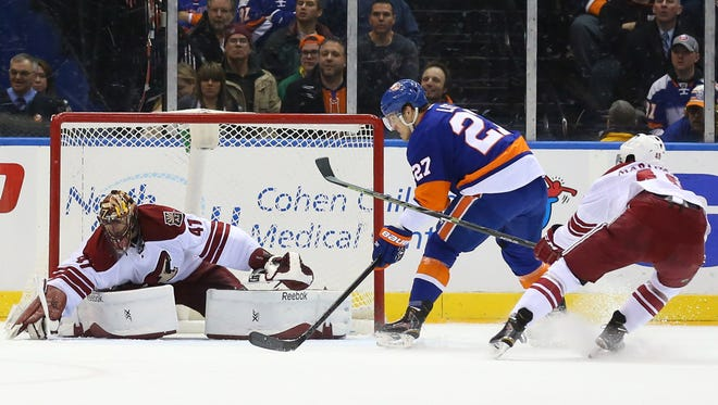 Feb 24, 2015: Arizona Coyotes goalie Mike Smith (41) makes a save on a shot by New York Islanders center Anders Lee (27) during the first period at Nassau Veterans Memorial Coliseum.