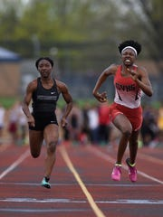Plymouth junior Reghan Draper (left) wins the 100-meter dash, followed by Clinton Valley's Reynei Wallace at the second annual New Balance Invitational track and field meet hosted by Farmington High School.