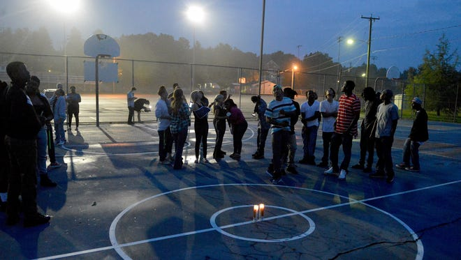 Candles are lit and held by those gathered for a vigil for Coleman Neeley on the basketball courts at Gypsy Hill Park on Tuesday, Aug. 19, 2014. Neeley was killed in a shooting Saturday in Fort Defiance.
