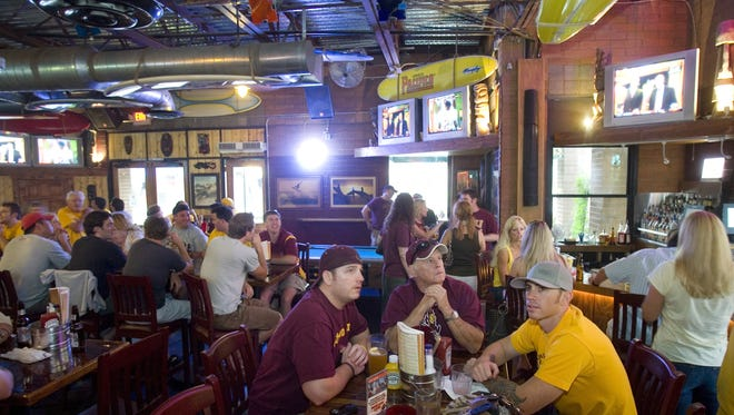 Football fans (front) Casey Hunter left, Coy Hunter center (of Glendale) and Travis Hunter (of Peoria) gather at the Tavern on Mill.