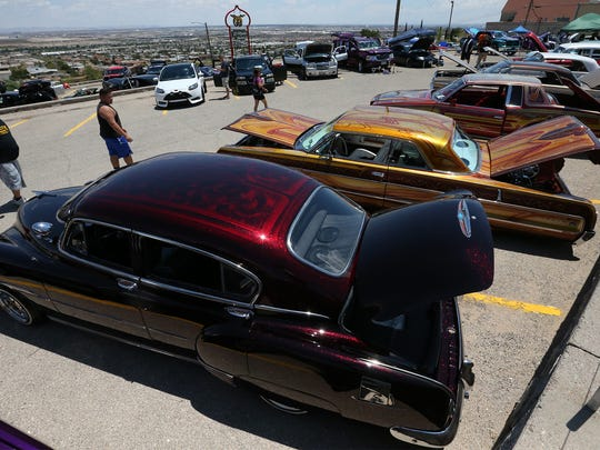 Classic and lowrider cars are lined up in neat rows