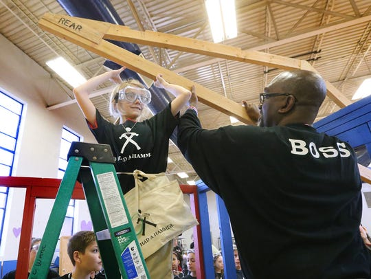 Fifth-grader Jordan Hawley eases part of the roof in