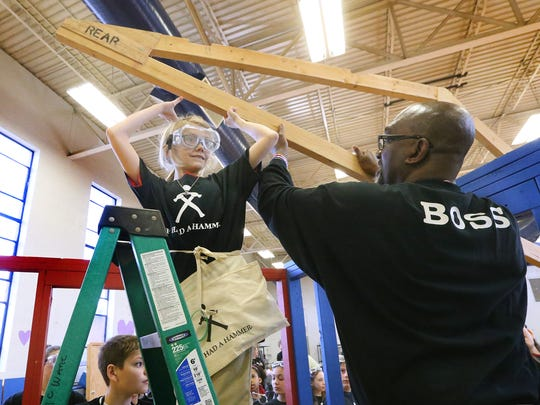 Fifth-grader Jordan Hawley eases part of the roof in place with the help of former NBA star Daryl Braden during the If I Had a Hammer: The Hammer Build Experience program at Hobgood Elementary Thursday, Feb. 23, 2017.