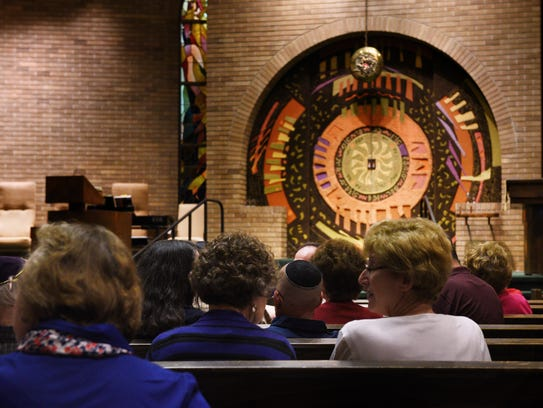 Congregants settle into the sanctuary at Temple Emeth