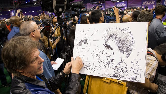 The Arizona Republic editorial cartoonist Steve Benson draws a caricature of New England Patriots QB Tom Brady during Super Bowl Media Day at U.S. Airways Center in Phoenix January 27, 2015. The New England Patriots will play the Seattle Seahawks Sunday February 1 in Super Bowl XLIX in Glendale.