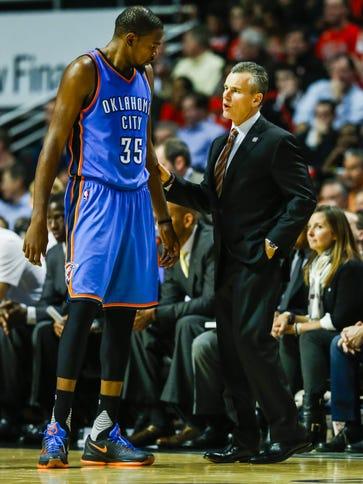 Oklahoma City Thunder coach Billy Donovan (R) talks