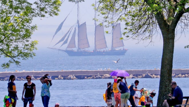 People enjoy the weather at the lakefront as the Denis Sullivan sails on Lake Michigan during the 31st annual family kite festival at Veterans Park in Milwaukee on Sunday.