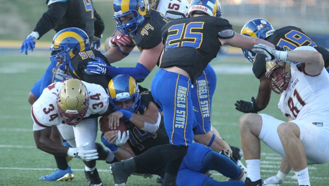 An Angelo State player tries to strip the ball away from Midwestern State running back Vincent Johnson (34) near the end zone during a Lone Star Conference game at LeGrand Stadium at 1st Community Credit Union Field on Saturday, Oct, 14, 2017. MSU handed ASU a 41-27 defeat.