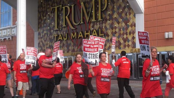 Striking union members walk a picket line outside the Trump Taj Mahal casino in Atlantic City, N.J. on Friday July 1, 2016. Local 54 of the Unite-HERE union went on strike against the casino, which is owned by billionaire investor Carl Icahn. (AP Photo/Wayne Parry)